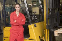 Warehouse worker standing by forklift - stock photo