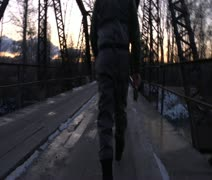 camera follows fly fisherman walking across bridge in winter - stock footage