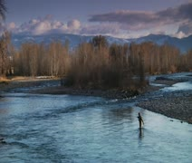 epic wide shot  of man flyfishing in River in wintertime - stock footage