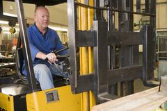 Warehouse worker in forklift - stock photo