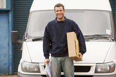 Deliveryperson standing with van holding clipboard and box smiling Stock Photos