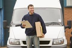 Deliveryperson standing with van holding clipboard and box smiling - stock photo