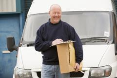Deliveryperson standing with van with clipboard and box smiling - stock photo