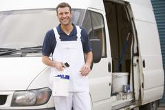 Painter standing with van smiling Stock Photos