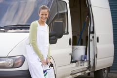 Painter standing with van smiling - stock photo