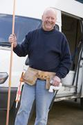 Plumber standing with van smiling - stock photo