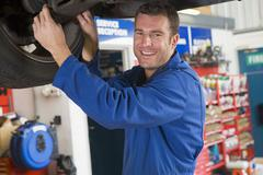 Mechanic working under car smiling Stock Photos