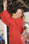 Mechanic working under car smiling - stock photo