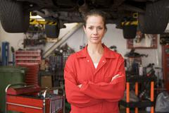 Mechanic standing in garage - stock photo