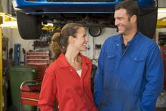 Two mechanics standing in garage smiling Stock Photos