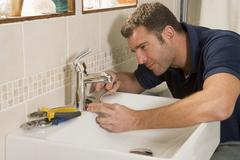 Plumber working on sink - stock photo