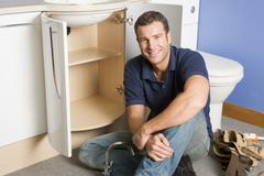 Plumber working on sink smiling - stock photo