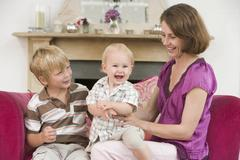 Mother in living room with baby and young boy smiling - stock photo