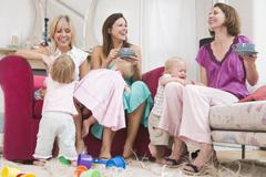 Stock Photo of Three mothers in living room with coffee and babies smiling