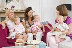 Stock Photo of Three mothers in living room with babies and coffee smiling
