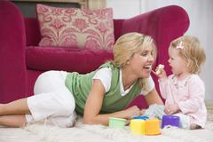 Mother in living room with baby eating banana and smiling - stock photo