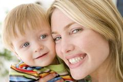 Mother and young boy indoors smiling Stock Photos