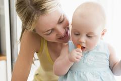 Mother and baby in kitchen eating carrot - stock photo