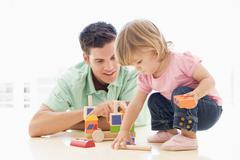 Stock Photo of Father and daughter indoors playing and smiling