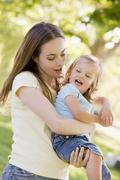 Mother holding daughter outdoors smiling Stock Photos