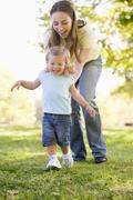 Mother and daughter playing outdoors smiling Stock Photos