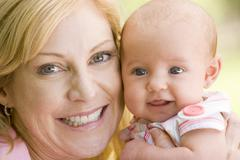 Mother and baby outdoors smiling - stock photo
