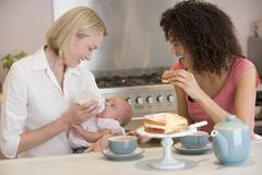 Mother and baby in kitchen with friend eating cake and smiling Stock Photos