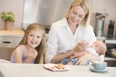 Mother feeding baby in kitchen with daughter eating cookies and smiling Stock Photos