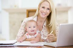 Mother and baby in dining room with laptop smiling - stock photo