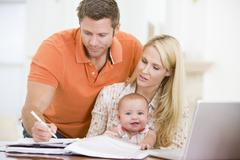 Couple and baby in dining room with laptop - stock photo
