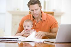 Father and baby in dining room with laptop - stock photo