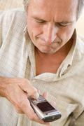Man using cellular phone indoors - stock photo