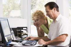 Couple in home office at computer frowning Stock Photos