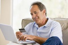 Man in living room with laptop and credit card smiling Stock Photos