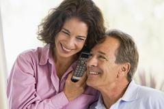 Couple indoors using telephone smiling Stock Photos