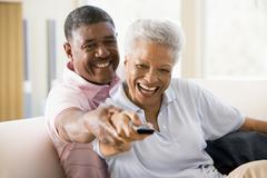 Couple in living room using remote control smiling Stock Photos