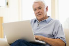 Man in living room with laptop smiling Stock Photos