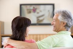 Couple watching television smiling Stock Photos