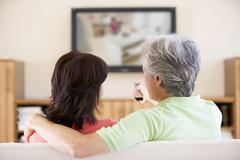 Couple watching television using remote control - stock photo