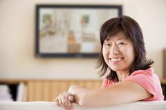 Woman watching television smiling - stock photo
