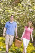 Couple walking outdoors with picnic basket smiling - stock photo