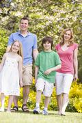 Family walking outdoors smiling - stock photo