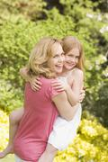 Mother carrying daughter outdoors smiling Stock Photos