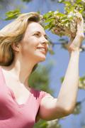 Woman standing outdoors holding blossom smiling - stock photo