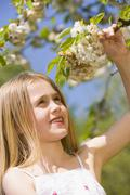 Young girl standing outdoors holding blossom smiling Stock Photos