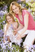 Mother and daughter outdoors holding flowers smiling - stock photo