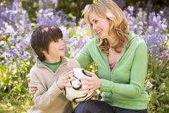 Mother and son outdoors holding ball smiling Stock Photos