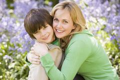 Mother and son outdoors embracing and smiling Stock Photos