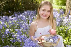 Young girl outdoors holding various eggs in basket smiling Stock Photos