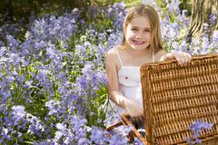 Young girl sitting outdoors with picnic basket smiling - stock photo
